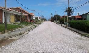 As ruas são de cascalho, conchinhas ou pedras. Poucos automóveis circulando.